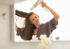Young woman blow drying hair in bathroom Stock Image