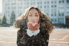 Young woman blow the snow from her hands. Winter, christmas and people concept Royalty Free Stock Photos