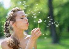 Young woman blowing away dandelion Royalty Free Stock Photography