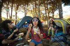 Young woman blowing bubble wand at campsite Royalty Free Stock Photos