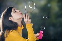 Young woman blowing bubbles. Outdoors Stock Image