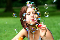 Young woman blowing bubbles. A view of a pretty young woman sitting in an open grassy area outdoors, blowing a cloud of bubbles royalty free stock image