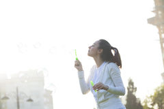 Young woman blowing bubbles. Young woman having fun and blowing bubbles outdoors Royalty Free Stock Photography