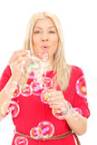 Young woman blowing bubbles Royalty Free Stock Images