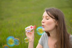 Young woman blowing bubbles Stock Image