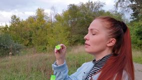 Young woman blowing bubbles in the park on a summer evening. stock footage