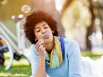 Beautiful woman blowing bubbles in park Stock Photos