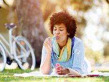 Beautiful woman blowing bubbles in park Royalty Free Stock Photos