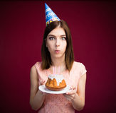 Young woman blowing candles on her cake Stock Photography