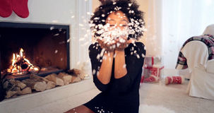 Young woman blowing Christmas confetti Royalty Free Stock Photography
