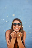 Young woman blowing confetti in the air and smiling Stock Photo