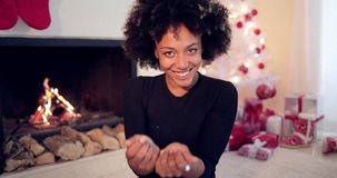 Young woman blowing confetti off her hands. Young african american woman with big afro haircut blowing white confetti off her hands as she celebrates Christmas stock footage