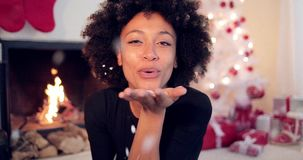 Young woman blowing confetti off her hands stock video