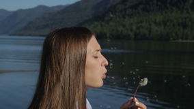 Young Woman Blowing Dandelion. Beauty Young Woman Blowing Dandelion Wishing stock footage