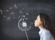 Young woman blowing dandelion on blackboard Stock Photography