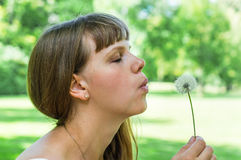 Young woman blowing dandelion flower Stock Photo