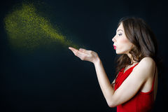 Young woman blowing at golden dust in her hands. Portrait of beatiful young woman blowing at golden dust in her hands, isolated on black background Royalty Free Stock Images