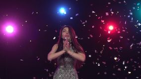 Young woman blowing with hands glitter confetti. Slow motion. Pretty young woman dancing and blowing with hands glitter confetti in front of disco style lights stock footage