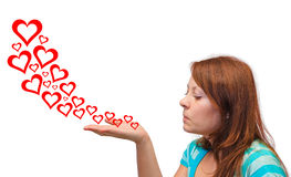 Young woman blowing hearts Royalty Free Stock Images