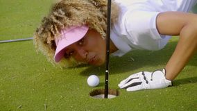 Young woman blowing her golf ball into the hole stock footage