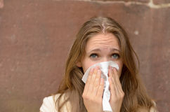 Young woman blowing her nose on a handkerchief Royalty Free Stock Photography