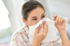 Young woman blowing her nose having cold. Young woman with cold blowing her nose Stock Image