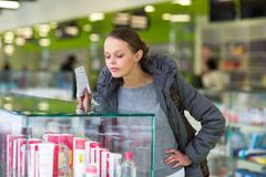 Young woman blowing her nose while in a modern pharmacy. Choosing pills to help her with the flu/cold shallow DOF; color toned image Royalty Free Stock Photography