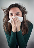 Young woman blowing her nose with paper tissue. Stock Photo