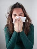 Young woman blowing her nose with paper tissue. Stock Photography