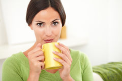 Young woman blowing on hot coffee Stock Image