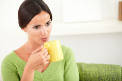 Young woman blowing into a hot coffee cup Royalty Free Stock Photography