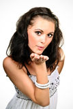Young woman blowing a kiss. Woman in white dress blowing a kiss isolated on white stock photography