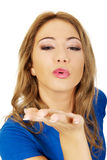 Young woman blowing a kiss. Royalty Free Stock Image