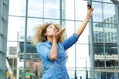 Young woman blowing kiss and taking selfie Stock Photo