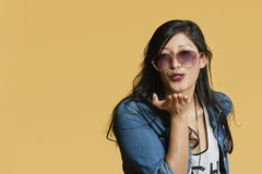 Young woman blowing kisses over colored background Royalty Free Stock Photos