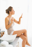 Young woman blowing on nails after applying nail polish Royalty Free Stock Images