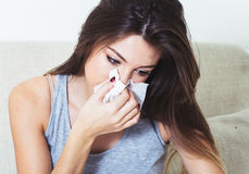 Young woman blowing nose in bed ill with temperature Stock Photography