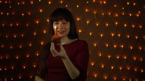 A young woman blowing out a candle on a cake next to the yellow lights. A young woman makes a wish and blowing out a candle on a cake against the background of