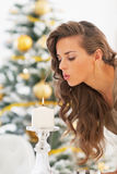 Young woman blowing out candle in front of christmas tree Royalty Free Stock Photography