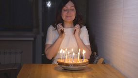 Young woman blowing out candles on holiday cake.  stock footage