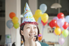 Young Woman Blowing Party Horn Stock Images