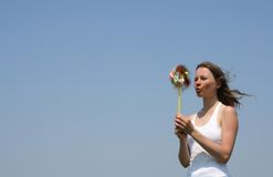 Young woman blowing a pinwheel Royalty Free Stock Images