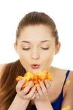 Young woman blowing rose petals. Beautiful teenage woman blowing rose petals Royalty Free Stock Images