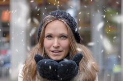 Young woman blowing snow at the camera Stock Images