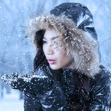 Young woman blowing snow on hands Stock Images