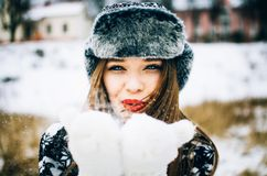 Young woman blowing snow. Handsome young woman wearing warm hat and mitten blowing snow in the winter nature Royalty Free Stock Image