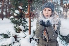 Young woman blowing snow in winter forest. Girl having fun outdoors stock image
