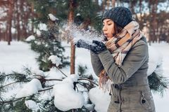 Young woman blowing snow in winter forest. Girl having fun outdoors stock photos