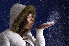 Young woman blowing snow wishe. Snowing on young woman in white wintercoat blowing snow wishes Royalty Free Stock Images