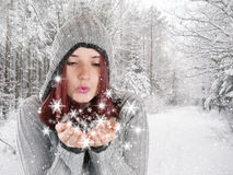 Young woman blowing snowflakes in winter landscape